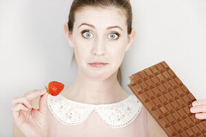 Beautiful young woman choosing to eat chocolate or a fresh strawberry.-1
