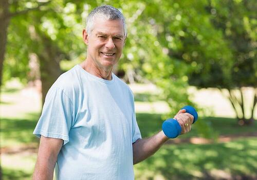 Portrait of a smiling mature man exercising with dumbbell at the park