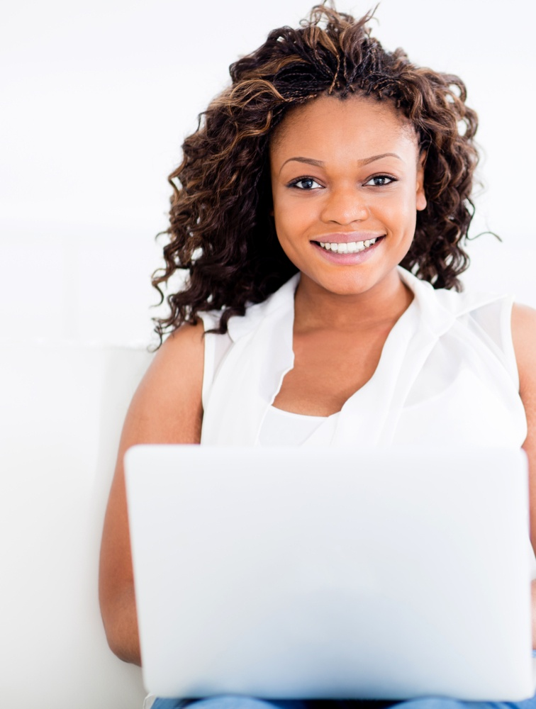 Woman working on a laptop looking happy