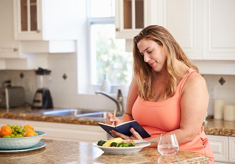 woman writing in food journal