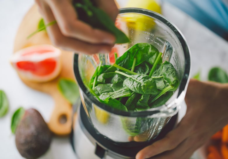 person putting spinach in blender