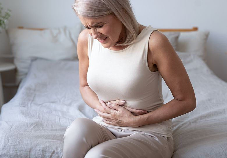 woman-with-stomach-pain-on-bed