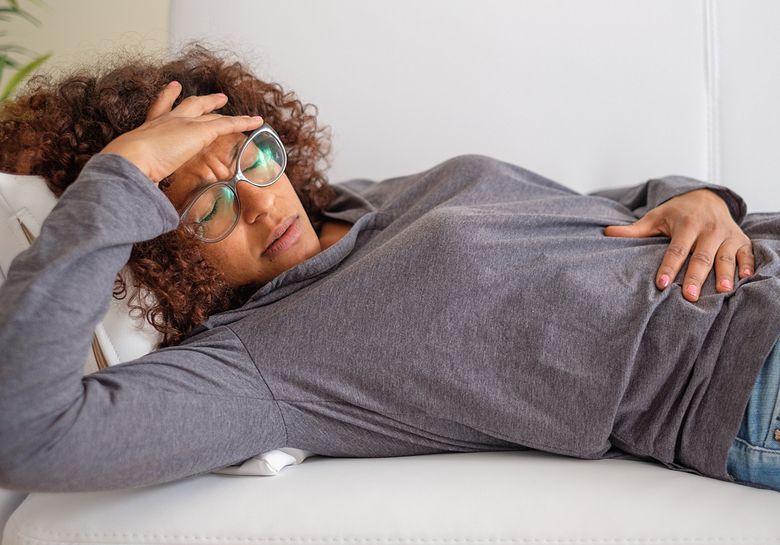 woman lying down with stomach pain